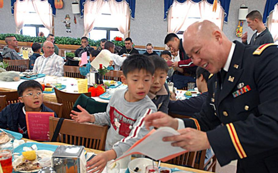 Second Lt. Tae H. Rose with Headquarters Headquarters Company, 1st Heavy Brigade Combat Team, 2nd Infantry Division hands out Thanksgiving cards to children from the My Home Orphanage at Camp Hovey, South Korea, on Thursday.