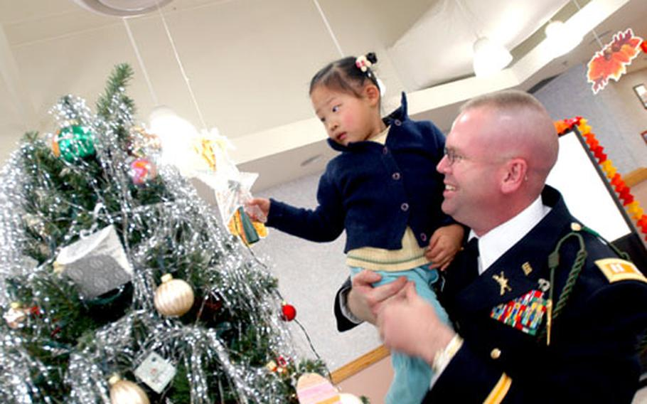 Capt. Dale Woodhouse, commander of Headquarters Headquarters Company, helps a little girl from the My Home Orphanage place a star on the Christmas tree.