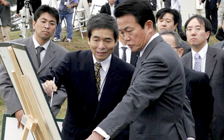 Naha Defense Facilities Administration Bureau Director General Masanori Nishi, left, briefs Foreign Minister Taro Aso, right, Friday about U.S. base relocation plans on Okinawa. Aso visited Schwab during a tour of Okinawa bases.