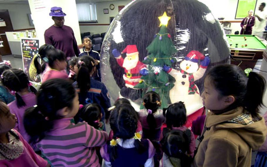 A group of girls from the the Sun Duk Orphanage check out the holiday decorations during a holiday visit at Yongsan Garrison, South Korea, on Friday.