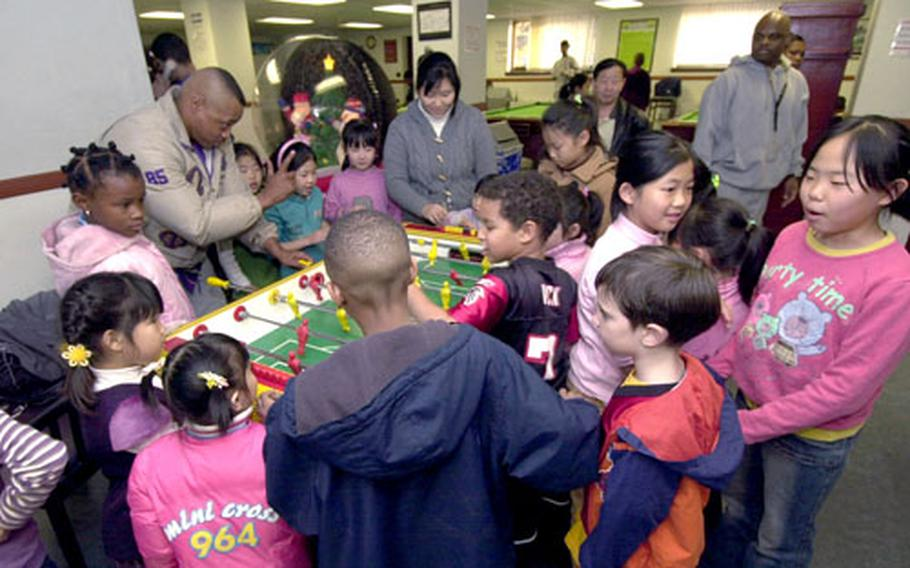 Marine Master Sgt. Jeffery plays foosball with girls from the Sun Duk Orphanage.