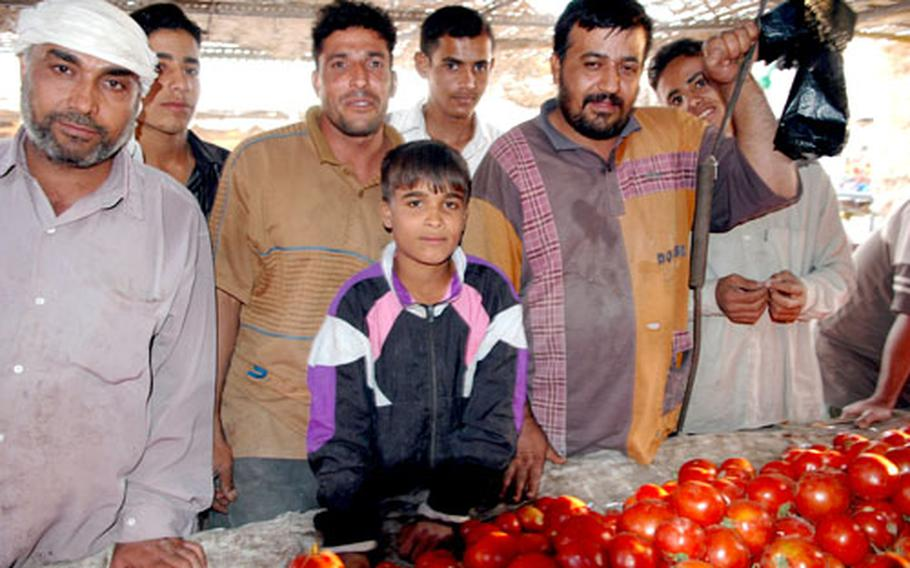 """Death by tomato: That's what vendor Radi Abd al-Hussein's 12-year-old son, center, wants for Saddam Hussein. His father, however, was more blunt: """"See you in hell,"""" he said."""