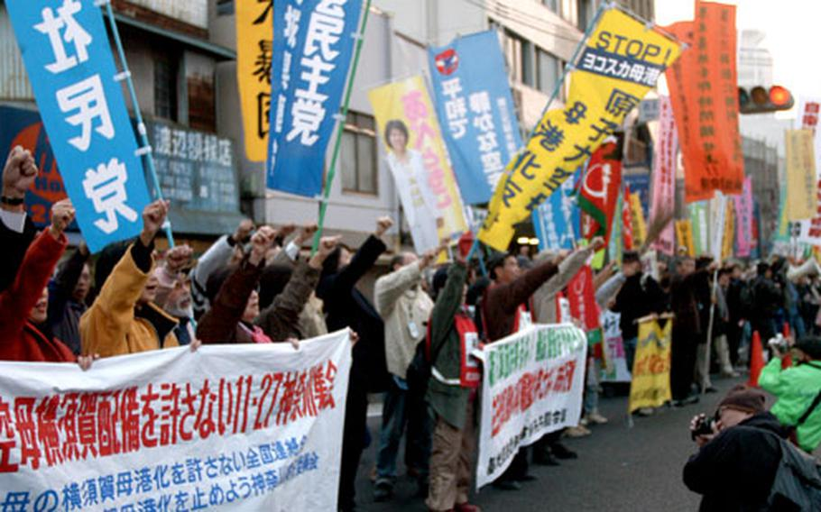 Protesters stop outside the main gate of Yokosuka Naval Base, Japan, on Sunday and chant their opposition to a number of recently announced U.S. military plans. Some 2,000 protesters marched from Yokosuka's Daiei Mall to Yokosuka Chuo station.