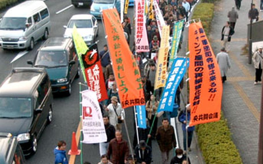 Protesters march along Route 16 in front of Yokosuka Naval Base.