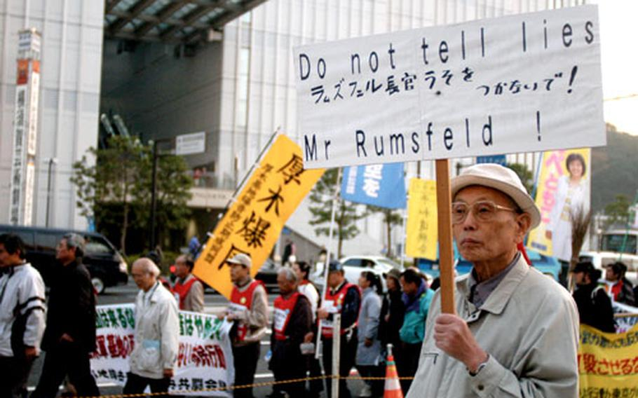 Protesters carry signs during their demonstration on Sunday against the scheduled arrival of a nuclear-powered aircraft carrier and a relocation of troops to Camp Zama.