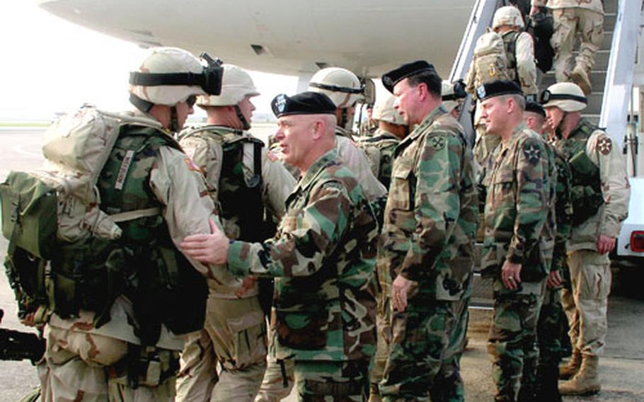 Troops of Army 2nd Infantry Division's Strikeforce brigade board a jetliner for Kuwait and eventual duty in Iraq on Aug. 10, 2004, at Osan Air Base, South Korea. Seeing them off are senior Army brass including, left, Gen. Leon J. LaPorte, the top American commander in South Korea. To LaPorte's right is Lt. Gen. Charles C. Campbell, commander of 8th U.S. Army, and to his right, Maj. Gen. John R. Wood, commander of the 2nd ID. LaPorte has announced that, after 38 years of service, he will retire Feb. 1.