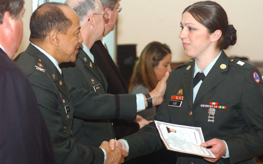 Spc. Albana Luli, originally from Albania, shakes hands with Col. Ervin Pearson, U.S. Army Europe deputy chief of staff, after receiving her certificate of citizenship.