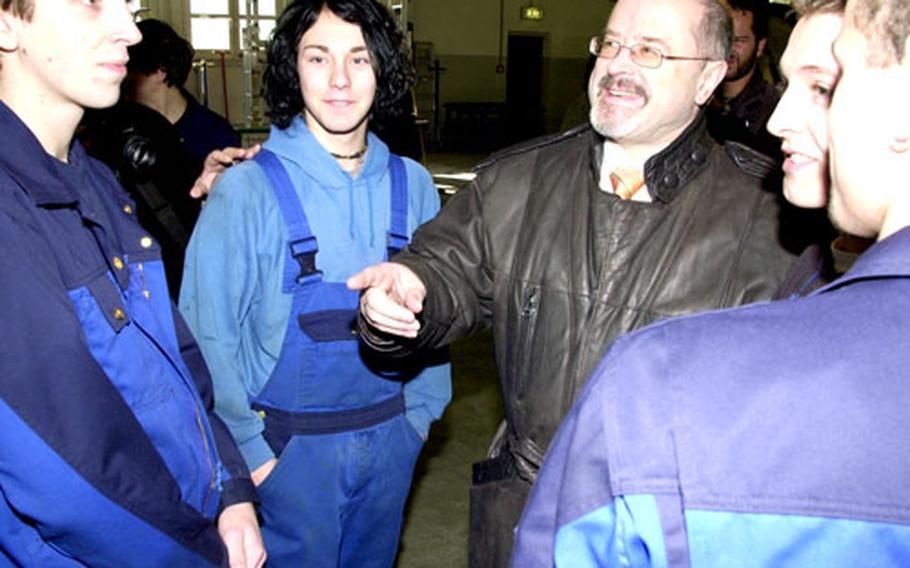 Bavarian State Secretary Jürgen Heike meets German apprentices at Grafenwöhr's Base Support Operations motor pool on Monday.
