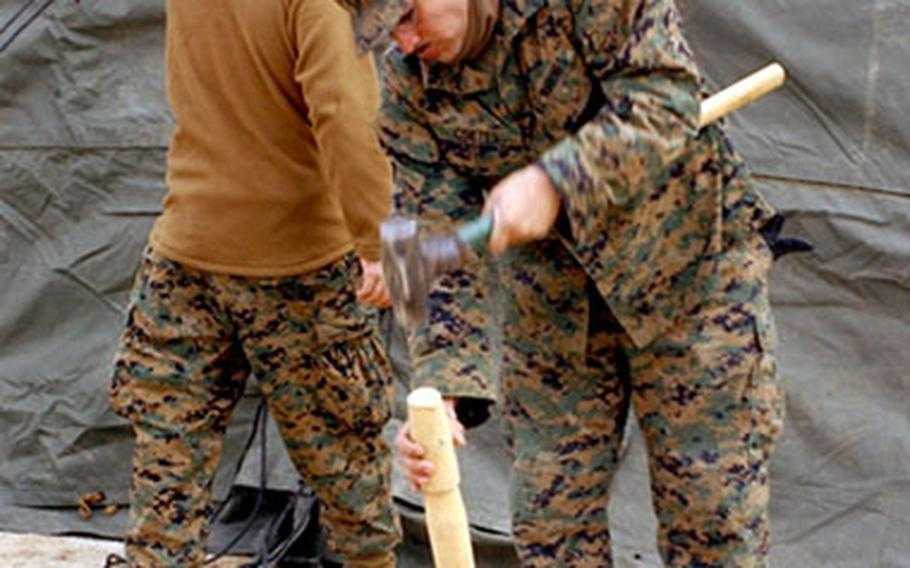 Lance Cpl. Israel Cortes, a radio technician with Marine Wing Support Squadron 171, hammers down a tent stake.