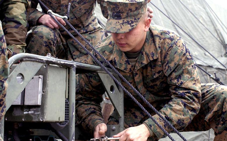 Lance Cpl. Israel Cortes, a radio technician with Marine Wing Support Squadron 171, hammers a tent stake Friday as Marines set up ROWPU Operations at Marine Corps Air Station Iwakuni's Penny Lake.