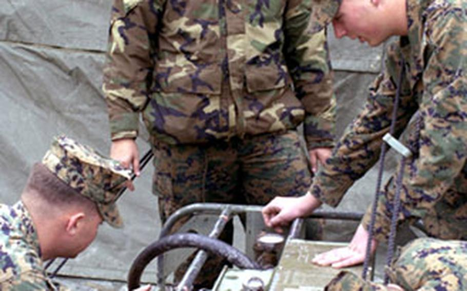 Basic hygiene equipment operators from Marine Wing Support Squadron 171 work with the water pump.