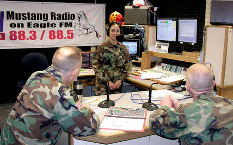 Camp Humphreys debuts its new weekly Area III radio show from the broadcast studios of AFN-Korea at Osan Air Base, featuring Area III commander Col. Michael J. Taliento, Jr., left, and Area III Command Sgt. Maj. Robert Frace, right. At the mike is Air Force Staff Sgt. Bronwyn Benito, sergeant-in-charge of radio operations.