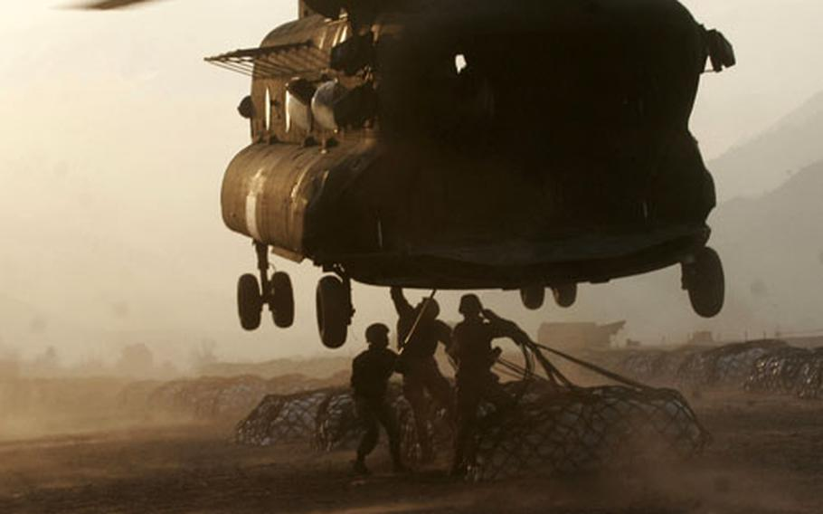 Marine landing support specialists attach external loads, or sling-loads, to the bottom of an Army CH-47 Chinook helicopter recently in Muzaffarabad, Pakistan. The Okinawa-based Marines currently are serving in Pakistan with Combined Medical Relief Team-3.