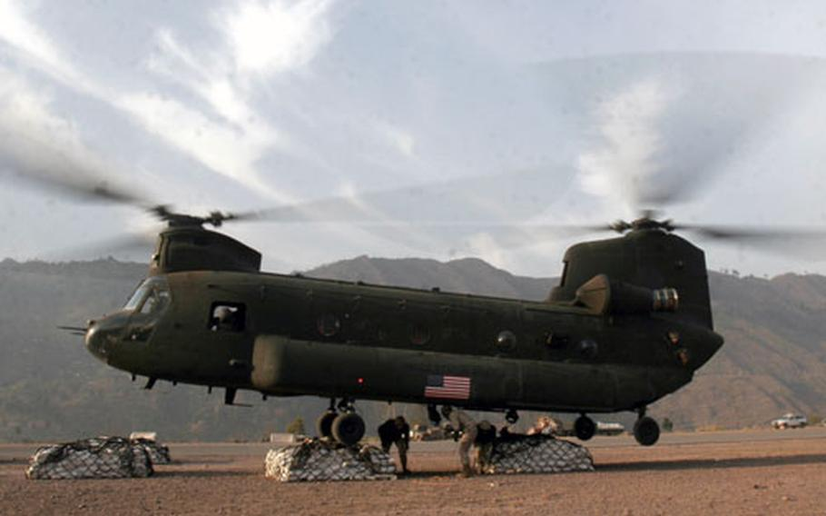 Marine landing support specialists attach external loads to the bottom of a Chinook helicopter.