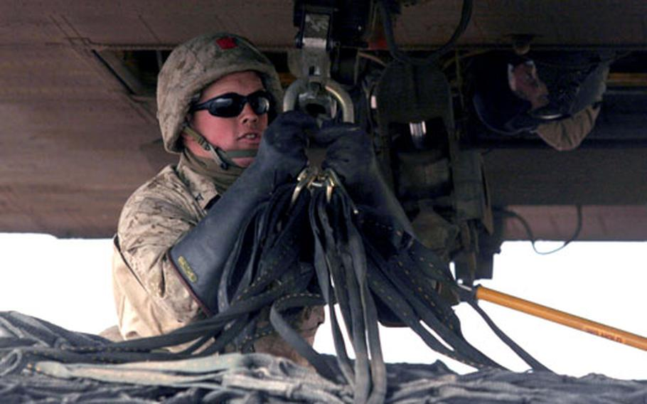 Lance Cpl. Jeffrey Radcliff, landing support specialist, connects an external load to the bottom of a Chinook helicopter. Radcliff and four fellow Marine landing support specialists have assisted in the delivery of more than 6.5 million pounds of food and supplies since Nov. 16, 2005, to earthquake victims in northern Pakistan.