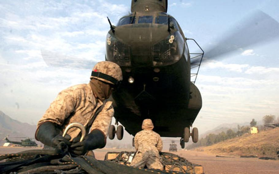 An Army CH-47 Chinook helicopter slowly lowers to hover above members of the Marine helicopter support team in Muzaffarabad, Pakistan, to pick up an external load.
