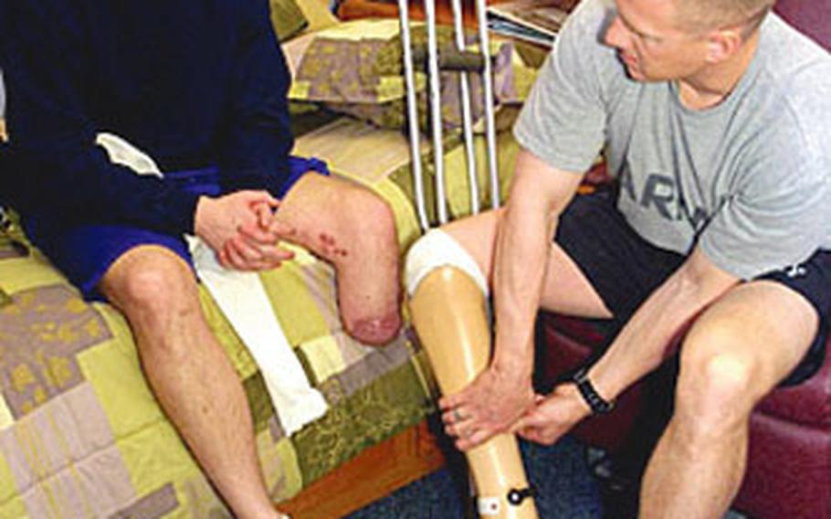 Capt. David Rozelle, right, talks about his prosthetic foot with Sgt. Justin Callahan at Walter Reed Army Medical Center in Washington. Rozelle recently told the Veterans Disability Benefits Commission that VA counselors should educate family members of wounded servicemembers about benefits and health care options.
