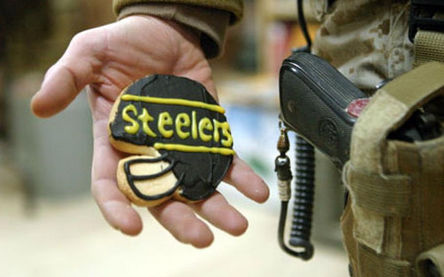 """A Marine from Pennsylvania stationed at Camp Taqqadum stands with a """"good luck cookie"""" that was sent from home to Iraq. Deployed troops and fans of the Pittsburgh Steelers and Seattle Seahawks hope their schedules will allow an opportunity to watch the Super Bowl."""