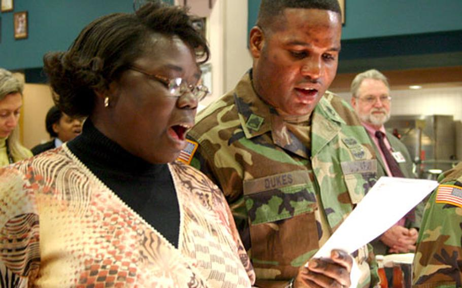 """Army Staff Sgts. Jennifer Simmons and John Dukes sing """"Lift Every Voice and Sing"""" during a luncheon Wednesday at Naval Support Activity Naples, Italy, that celebrated Black History Month and honored the Rev. Martin Luther King Jr."""