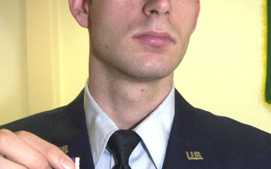 Senior Airman Joseph Wilson holds the Purple Heart he recently received for injuries he sustained in Iraq last year. Wilson was manning the 50-caliber gun in an armored truck when an improvised explosive device detonated among the convoy.