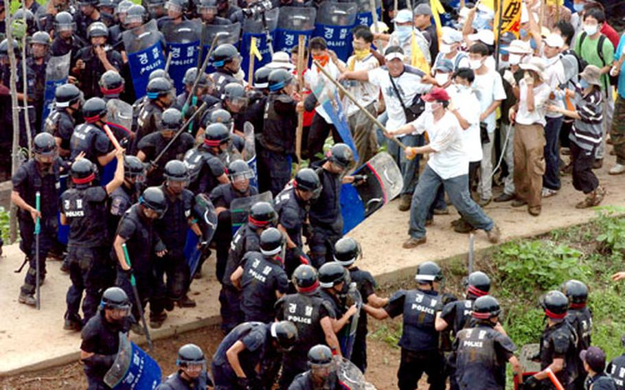 South Korean riot police battle demonstrators outside Camp Humphreys in Pyongtaek, South Korea, in July 2005. Korean National Police say 893 South Korean riot police were injured during protests last year.