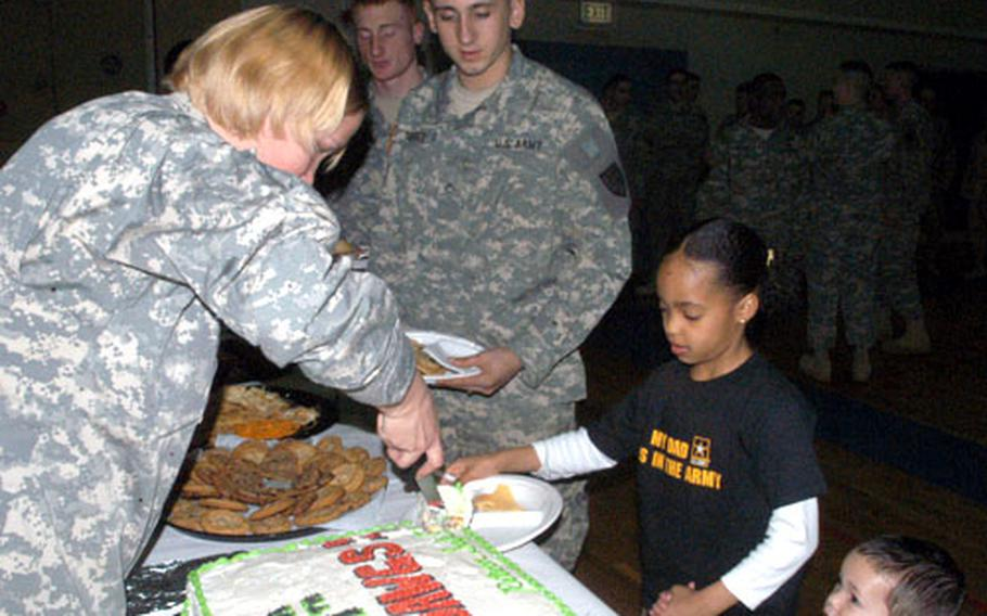 Nine-year-old Brianna Wills holds the hand of her 2-year-old brother, D.J., in front of Spc. Jose Torres as cake is served Thursday at a predeployment ceremony for the Stuttgart-based 554th Military Police Company. Brianna and D.J. are the children of Sgt. David Wills of Headquarters Platoon.