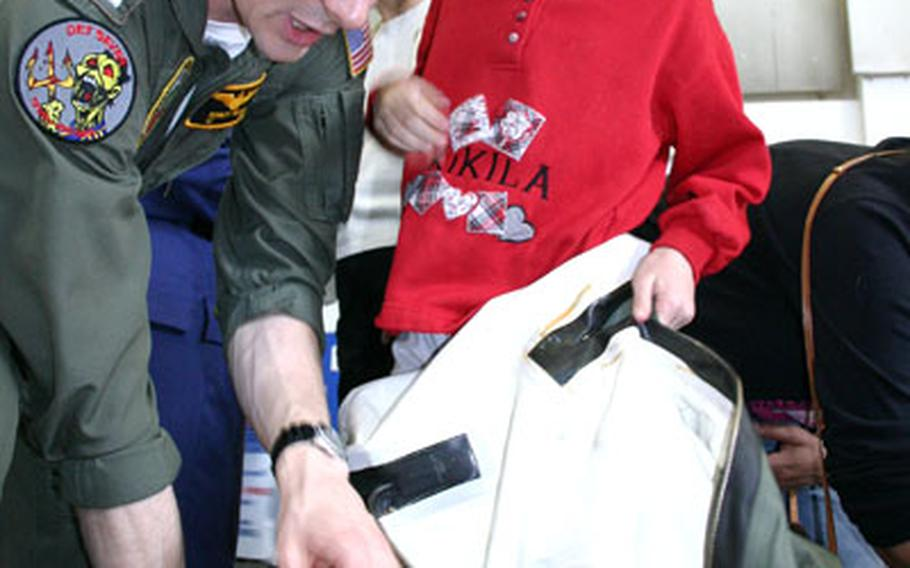"""Lt. Bobby Maslar, a C-26 pilot for the U.S. Navy, helps 8-year-old Isabella Cunningham don a """"dry"""" flight suit, a uniform aircrew wear when flying over cold water, during the annual career day at Naples Elementary School."""