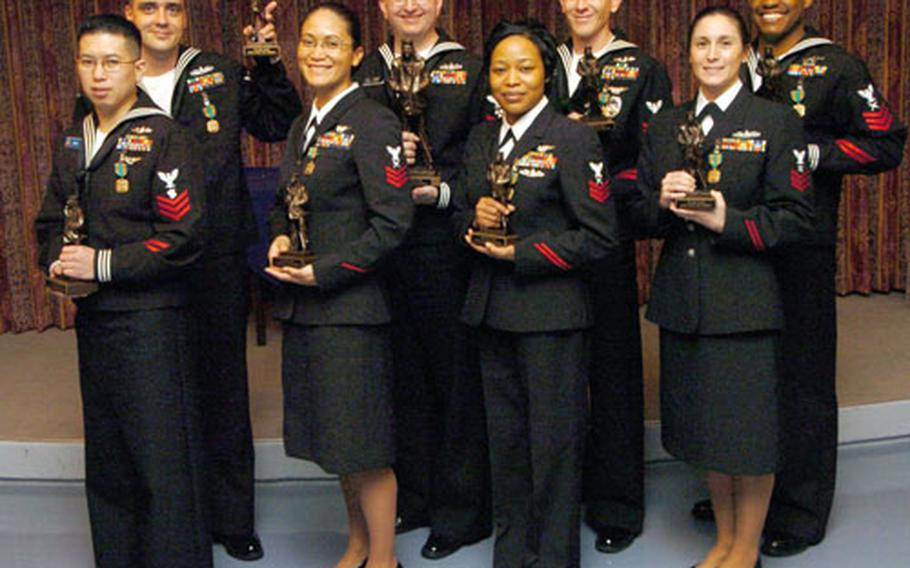 A group of eight petty officers 1st class from commands across Japan hold the awards Adm. James Kelly presented them Thursday. Top row, from left, are John Poole, Paul Kirby, David Thomas and Terrence Ingram. Front row from left are Reynaldo Giron, Damaris Havens, Latricia Robinson and Sarah King. Charity Broomfield, currently deployed, also received the award. Kirby was named Sailor of the Year for Japan.