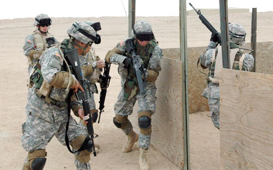 Soldiers from a medical unit, Company C, 47th Forward Support Battalion, practice building entry at an urban terrain training range outside Camp Buehring in Kuwait.