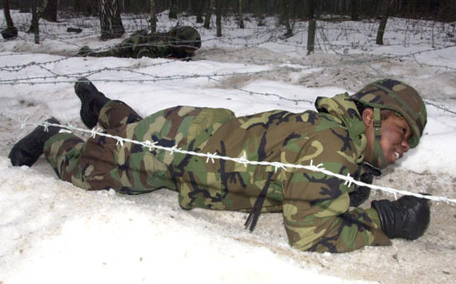 A 191st Ordinance Battalion soldier crawls under barbed wire on the obstacle course.