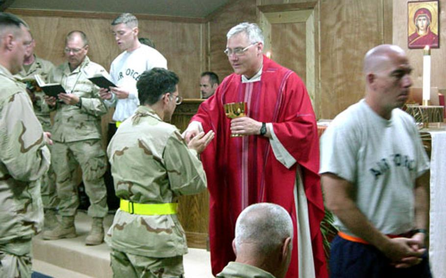 The Rev. Gary Linsky, a lieutenant colonel, Roman Catholic priest and the command chaplain for U.S. Forces Japan, 5th Air Force and 374th Airlift Wing at Yokota Air Base, Japan, gives communion during Mass at Balad Air Base, Iraq.