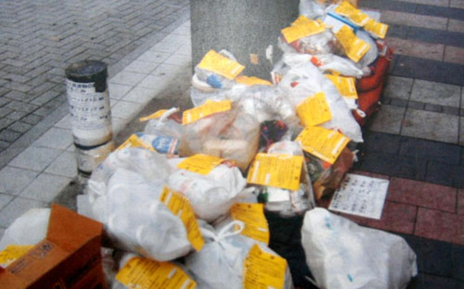 The yellow notices are warnings on unsorted trash left by residents of the City of Yokosuka. The city and Yokosuka Naval base officials made a recent push to educate Naval personnel living off-base on the proper way to dispose of trash.