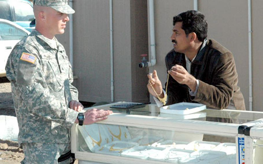 A soldier barters with a jewelry merchant at the Sunday bazaar, a regular weekend activity at Camp Buehring, Kuwait.