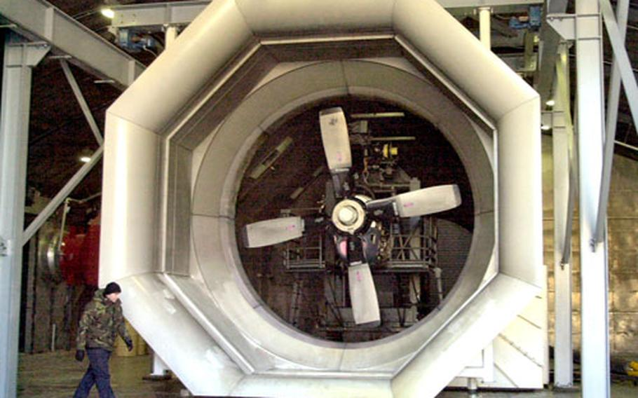 "An airman walks past a C-130 prop engine inside Ramstein Air Base's ""Hush House."""