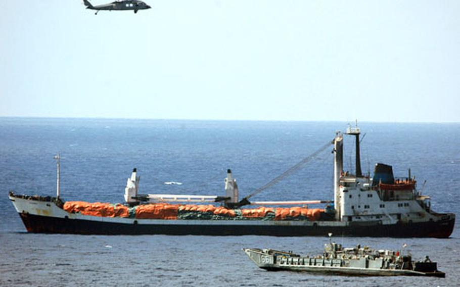 A Landing Craft Utility boat from USS Nassau approaches the port beam of the motor vessel al-Manara as a MH-60S Seahawk helicopter passes overhead.