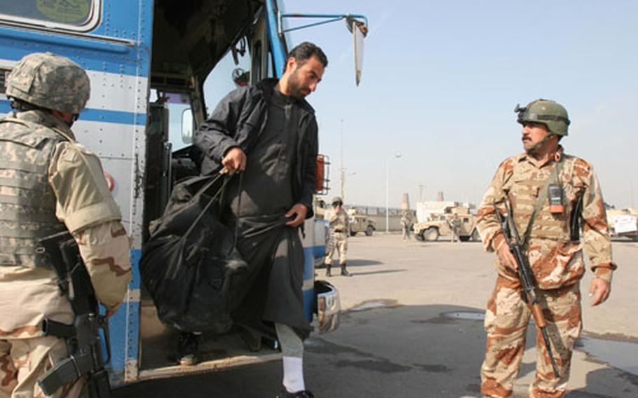 An Iraqi detainee walks from a bus at a central bus station after being released from a Baghdad jail on Sunday.