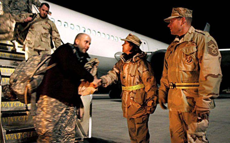 376th Air Expeditionary Wing vice commander Col. Pamela Milligan and Chief Master Sgt. Phillip Cherry hit the tarmac just before dawn to welcome incoming troops to Manas Air Base, Kyrgyzstan. Base officials make a point to personally greet large groups of troops transiting through Manas to Afghanistan.
