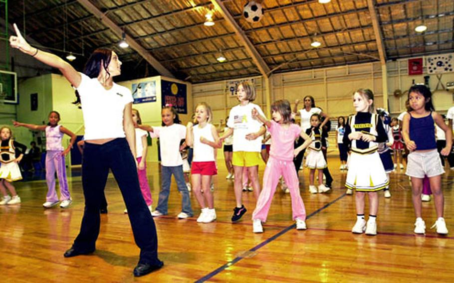 St. Louis Rams cheerleader Angeline O'Neal, left, leads young cheerleaders in dance moves during a clinic held Sunday at Kadena Air Base's O'Connor Gym.