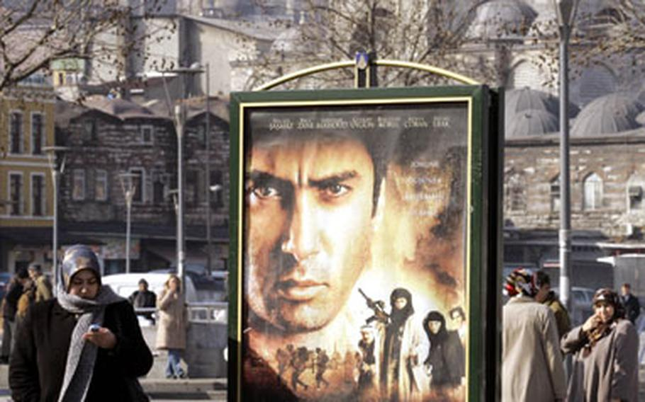 """A woman stands next to a billboard featuring the new Turkish movie """"Valley of the Wolves Iraq"""" in Istanbul, Turkey. Tickets for the movie, the latest of a genre of pop culture works feeding off growing anti-American sentiment in Turkey, are selling out across the country."""