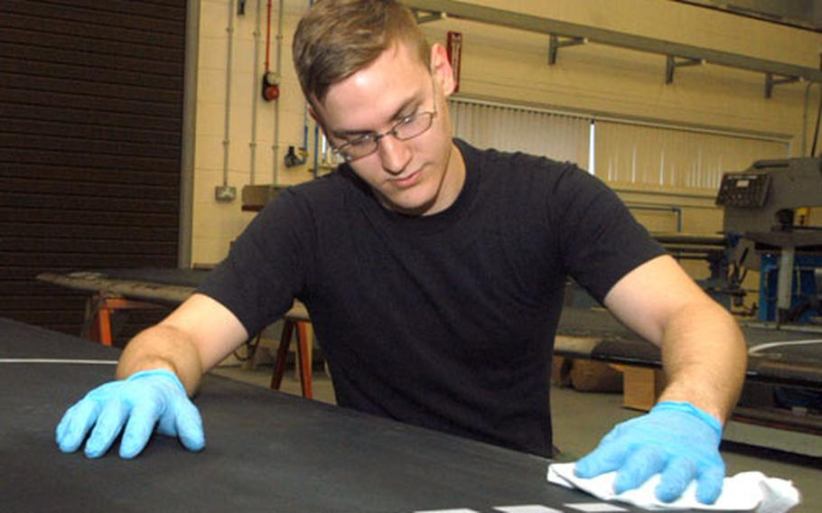 Senior Airman Niall Oxendale, an aircraft structural maintenance journeyman with the 100th Maintenance Squadron, fixes a MH-53 Pave Low helicopter blade.