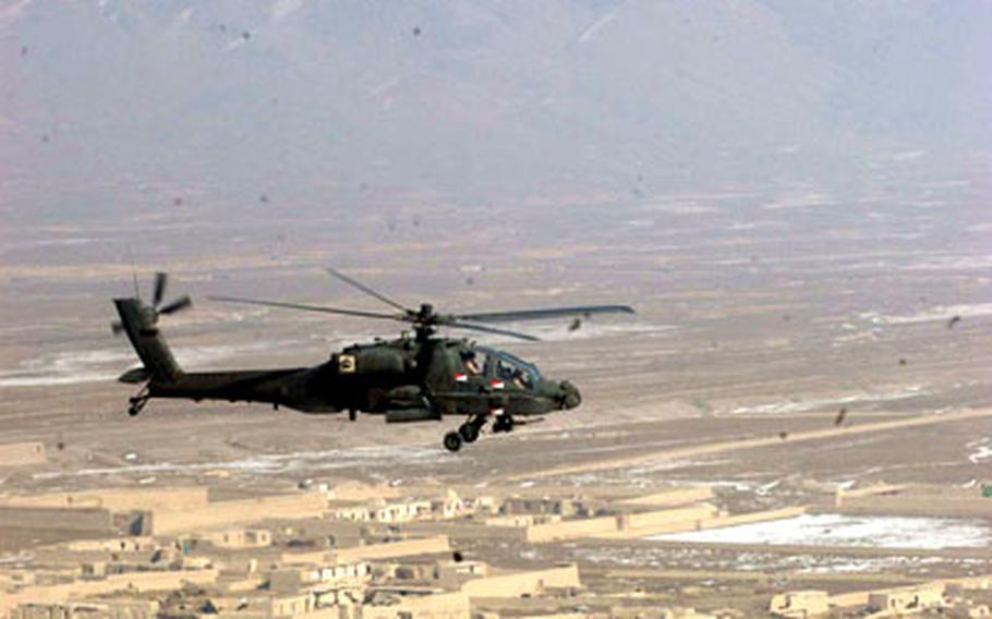An Apache helicopter glides over patches of snow outside of Kabul, Afghanistan, while escorting a Black Hawk helicopter that was transporting a general officer.