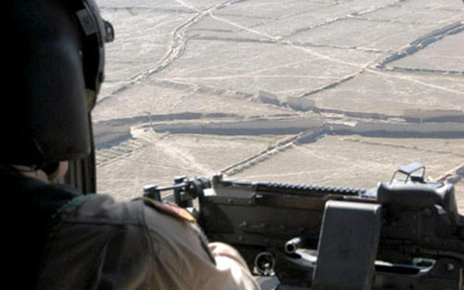 Spc. Sean Lewis looks out at the Afghan countryside over the turret of his machine gun as the Black Hawk he's aboard makes the short run between Bagram Air Base and Kabul. This flight took only about 15 minutes; others last for several hours.