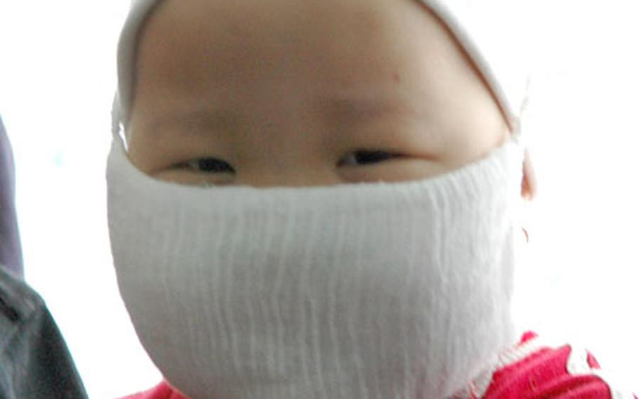 Five-year old Darica peers out from behind her mask.