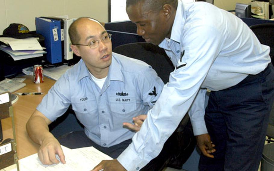 Petty Officer 2nd Class Gabriel Young, seated, talks with Petty Officer 3rd Class Joseph Kpulun at the Naval Support Activity Personnel Support Detachment in Naples, Italy. Both work in the customer service section as personnel specialists, but, until a recent rating merger, they had different jobs. Young used to be a personnelman and Kpulun used to be a disbursing clerk. The ratings were combined in October.