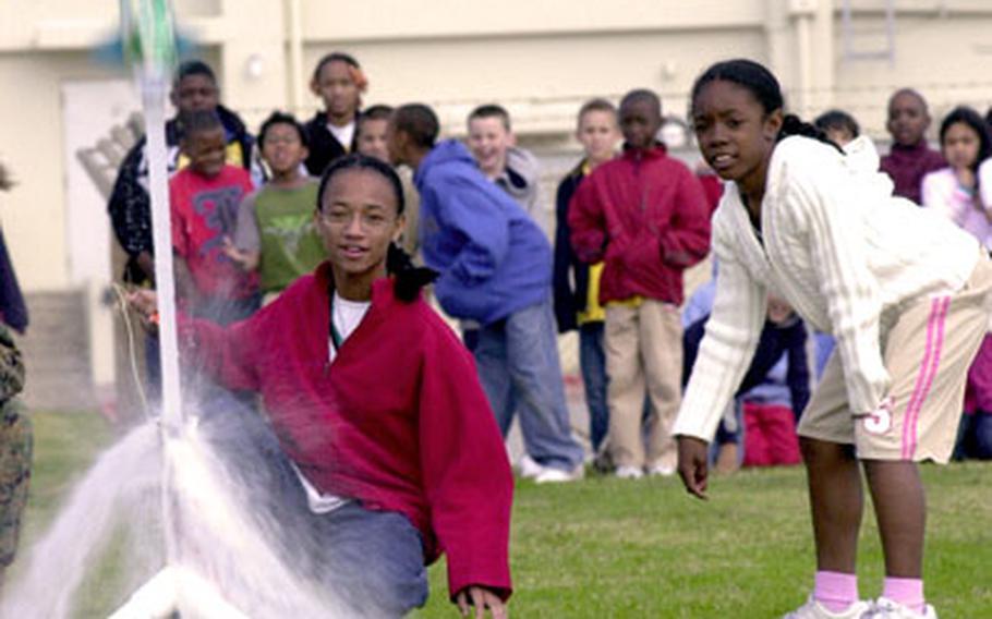 Kinser Elementary School fifth-graders Jasmine Vaughn, left, and Denise Jones watch as their water bottle rocket takes flight Tuesday.