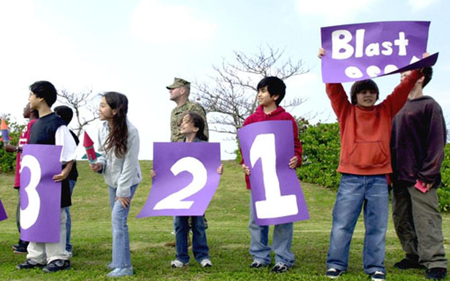Kinser Elementary students perform a countdown Tuesday as the fifth-grade class prepares to launch water-bottle rockets.