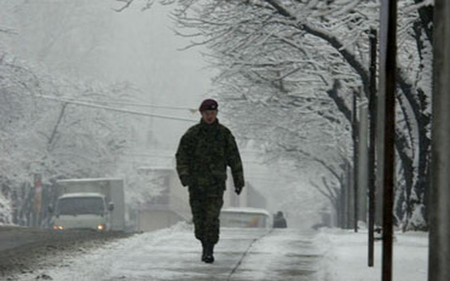 A soldier walks along the snowy I Corps Boulevard on Yongsan Garrison, South Korea, on Tuesday morning.