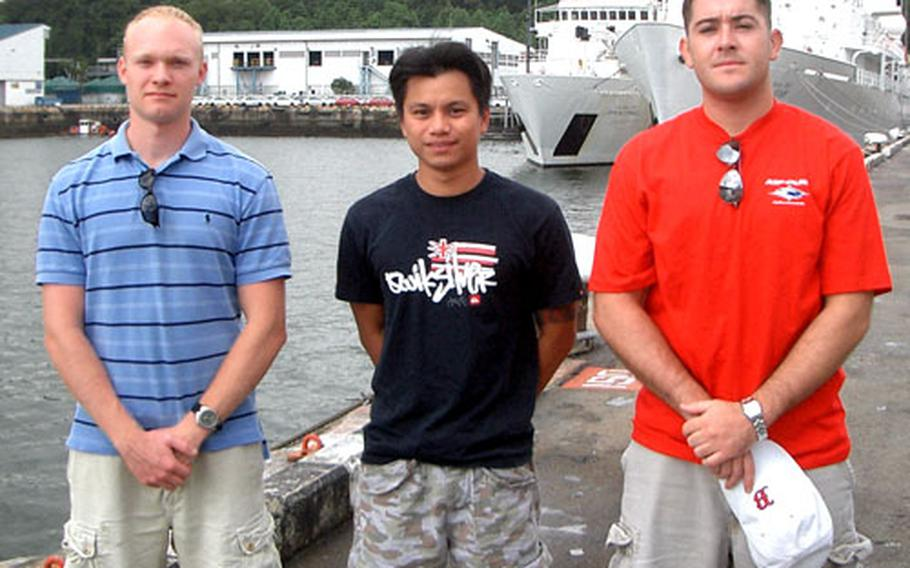 A machete attack victim in Singapore received emergency medical attention from these three men off the USNS John McDonnell. They are, from left, Merchant Mariner 3rd Mate Colin Campbell, U.S. Navy Petty Officer 2nd Class Paulryan Judi and Seaman Gregory Chaney.