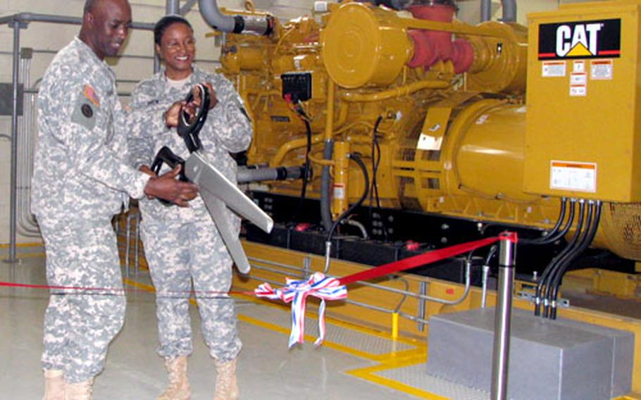 Army Col. Edric A. Kirkman, commander of the 516th Signal Brigade, and Lt. Col. Maria R. Drew, commander of the 58th Signal Battalion, prepare to cut the ribbon at Tuesday's official start-up of a new $11.7 million power plant on Fort Buckner, Okinawa.