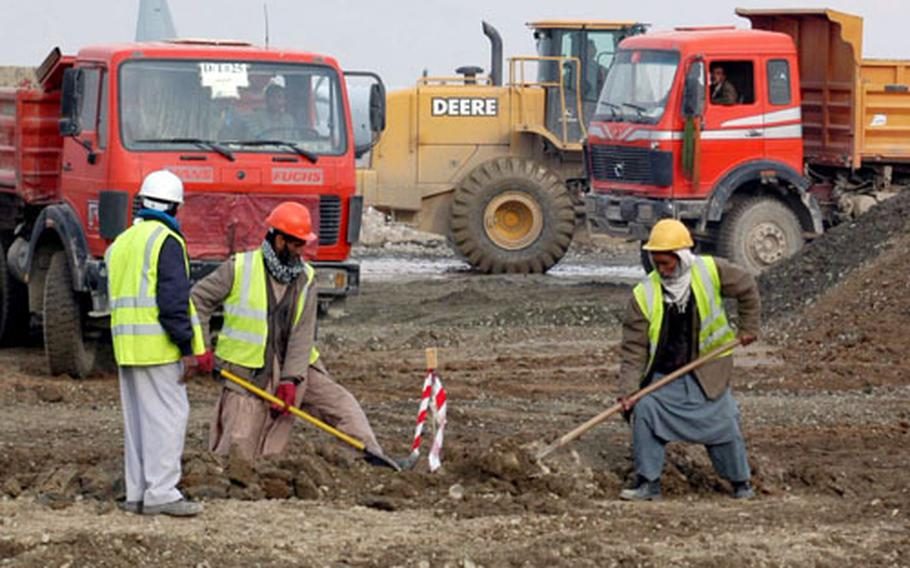 Afghan workers help move dirt as part of the work on a series of projects that will add a second runway and additional ramps to Bagram Air Base in Afghanistan. The new runway should be operational in September, with other parts of the project completed by next spring.